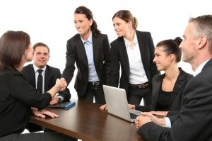 A_Group_Of_Six_People_Agreeing_On_Matters_With_Two_People_Shaking_Hands_In_The_Middle