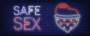 "A lit up sign saying, ""Safe Sex"", with a heart wearing a form of contraceptive next to the words."