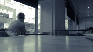 Girl sitting alone in a cafe.