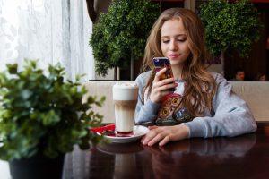 girl on phone drinking coffee