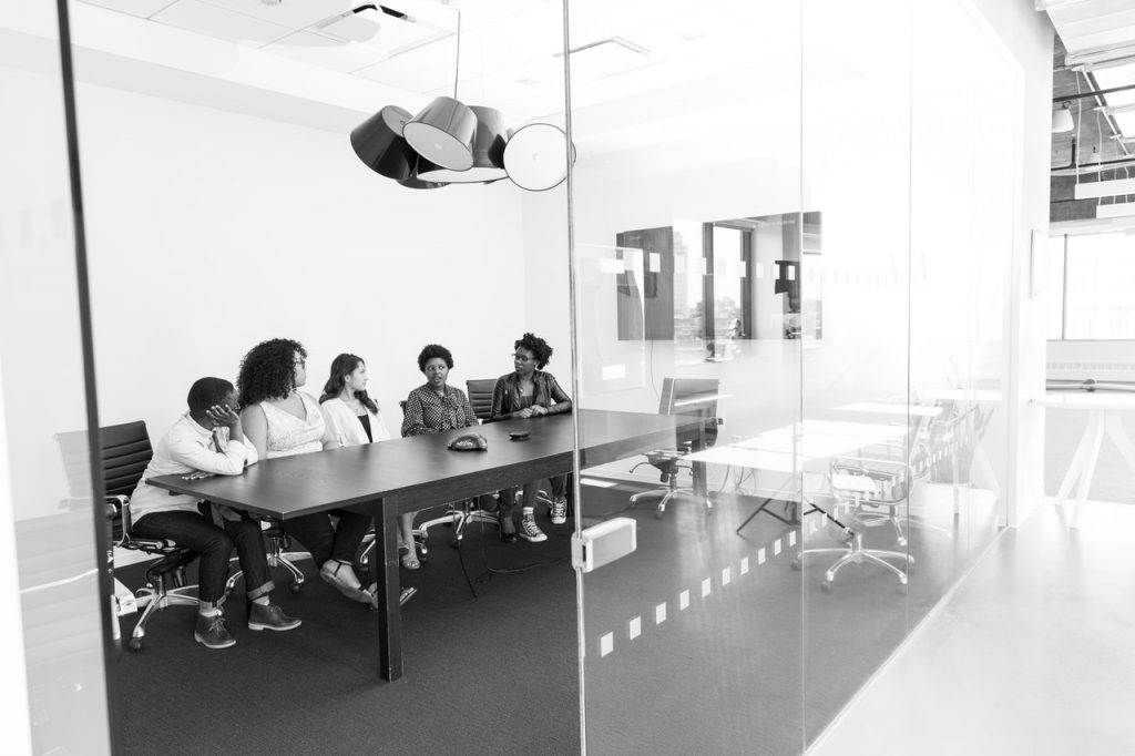 black and white image of women sitting at a table in a glass-walled office.