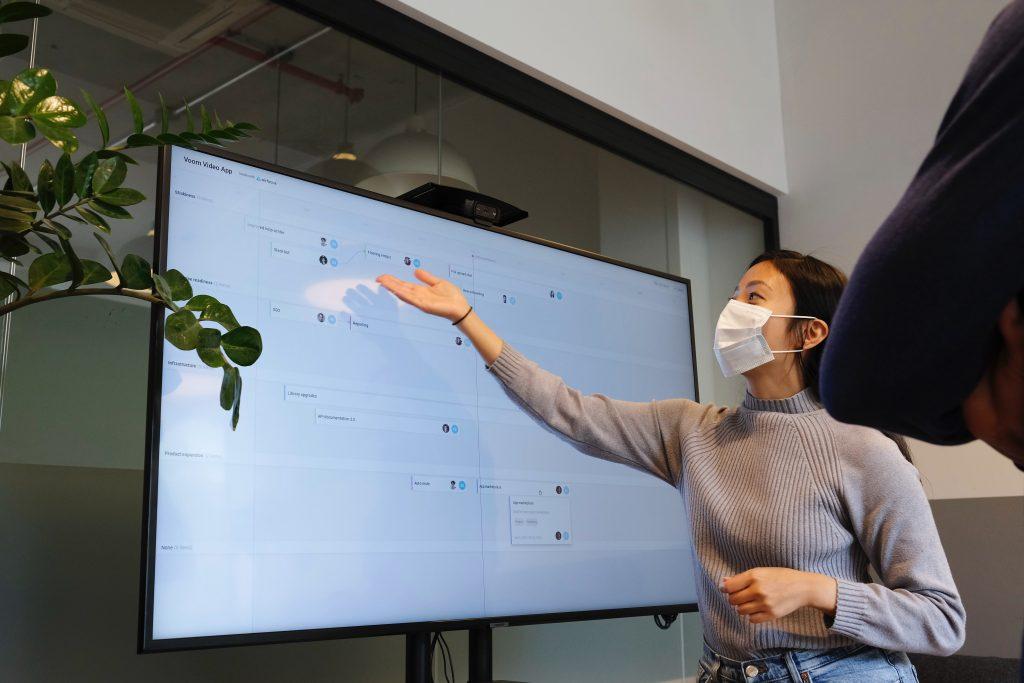 Woman presenting at TV display wearing a mask