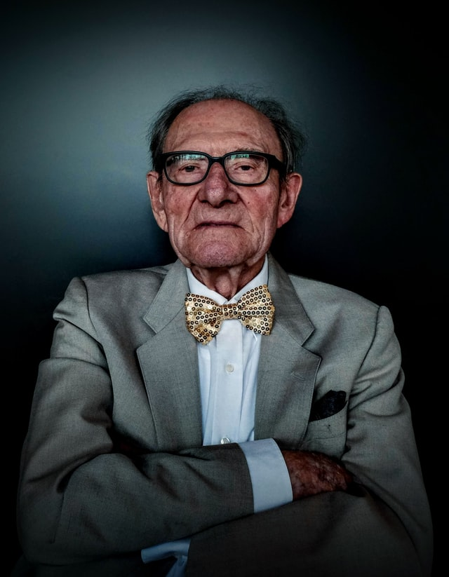 Elderly White man in business suit wearing a business suit and bow tie