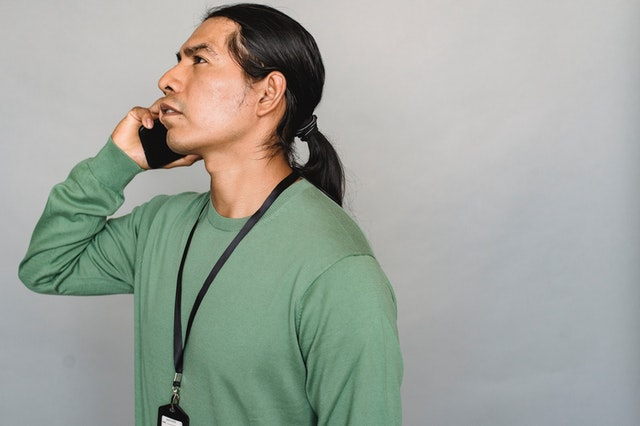 Native American man in green shirt standing in profile and talking on a mobile phone