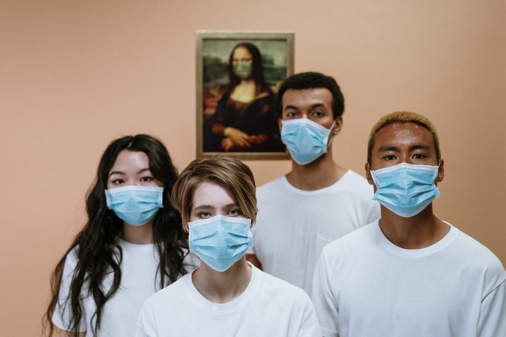 Four people standing in a room wearing hospital masks and white T-shirts. A picture of the Mona Lisa is on the wall behind them wearing a mask.
