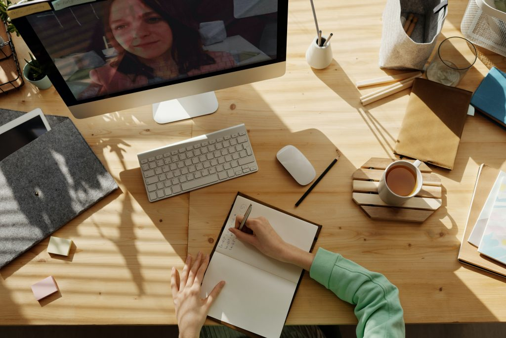 hands writing in notebook at a desk. Desktop computer on desk shows a virtual meeting