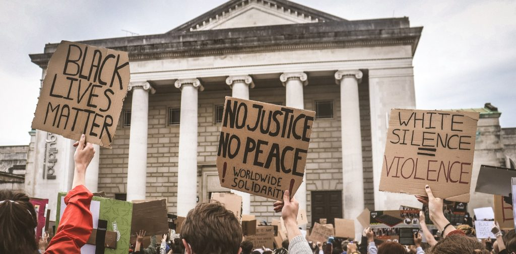 black lives matter protest. three cardboard posters showing: black lives matter, no justice/ no peace, white silence=violence