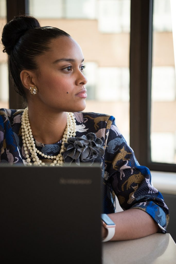 Close-up of African American business woman sitting in an office in front of a laptop, in profile. Not smiling.